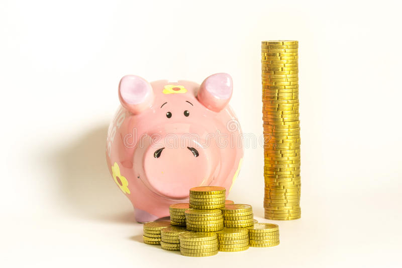 Piggy-bank with coins. Yellow coins in different layout with a pink piggy-bank royalty free stock photography