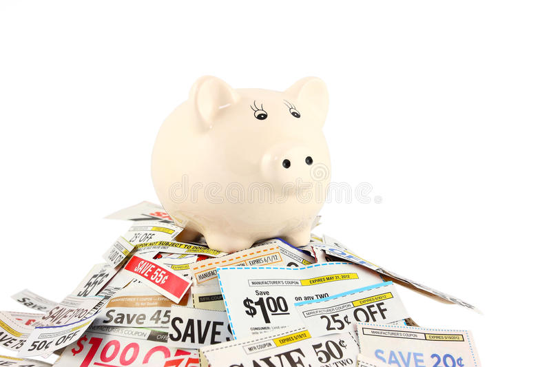Piggy Bank On Coupons. One ceramic piggy bank standing on top of a pile of coupons. Saving money concept stock photos
