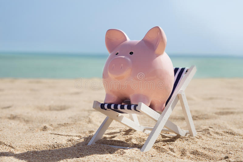 Piggy bank with deckchair. On Sandy Beach royalty free stock images