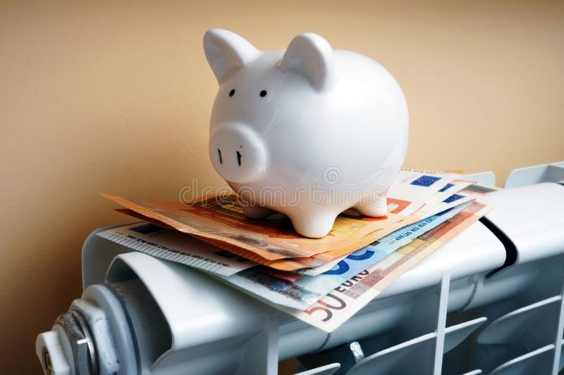 Piggy bank and euro banknotes on the heating radiator. royalty free stock image