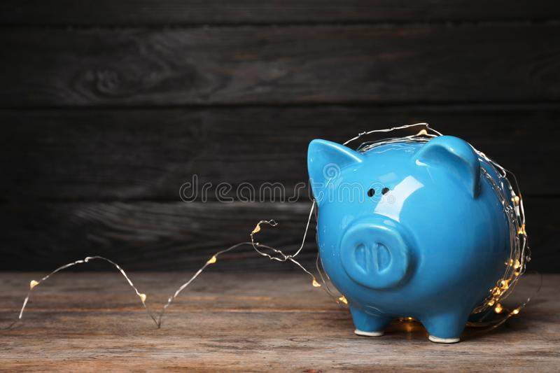 Piggy bank with fairy lights on wooden table. Space for text stock photo