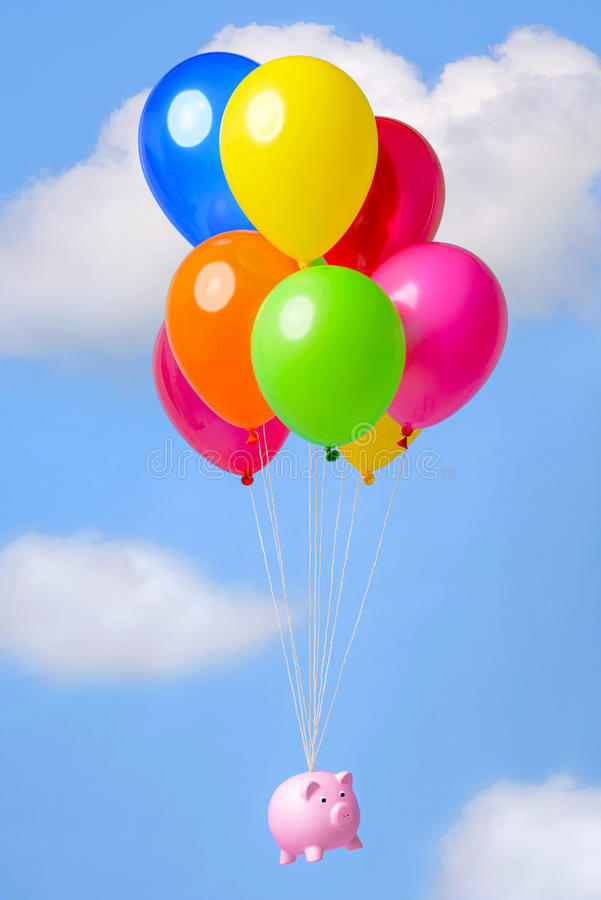 Piggy Bank floating through the sky on balloons stock photo