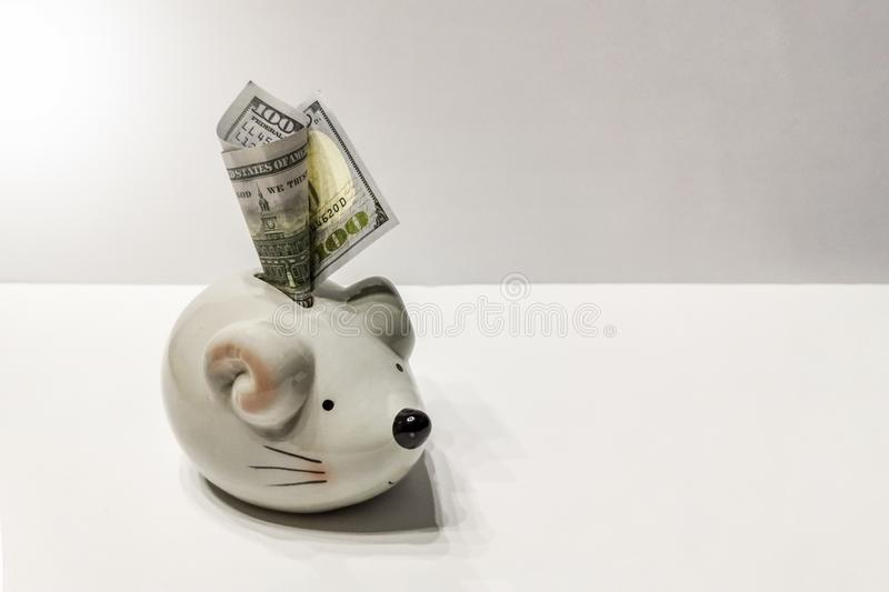 Piggy bank in the form of a rat with 100 dollars inserted into it. Chinese New Year 2020 concept. royalty free stock photography