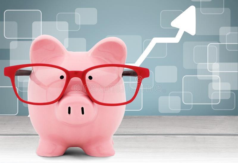 Piggy bank with glasses on the desk royalty free stock photos