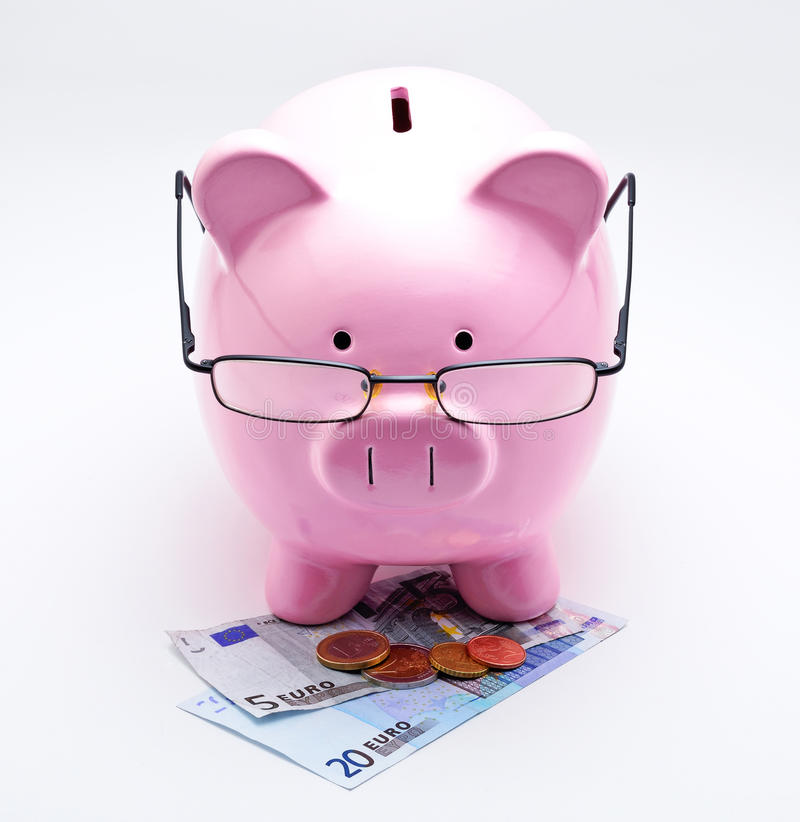 Piggy bank with glasses on Euros. Illustrating concepts of money royalty free stock photography