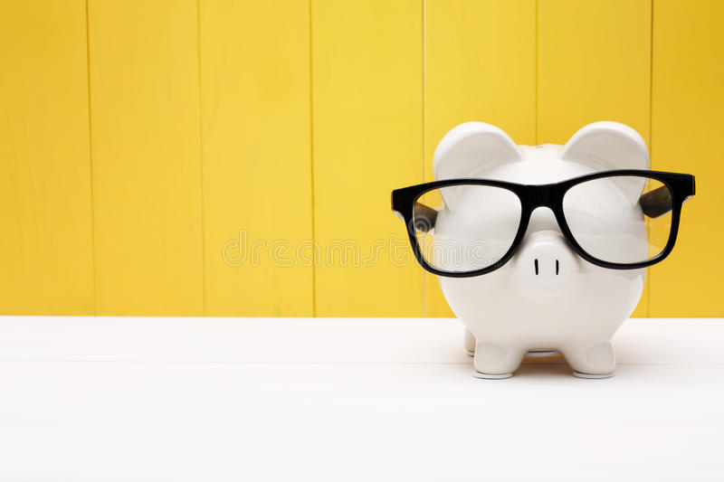 Piggy bank with glasses over yellow wooden wall stock image