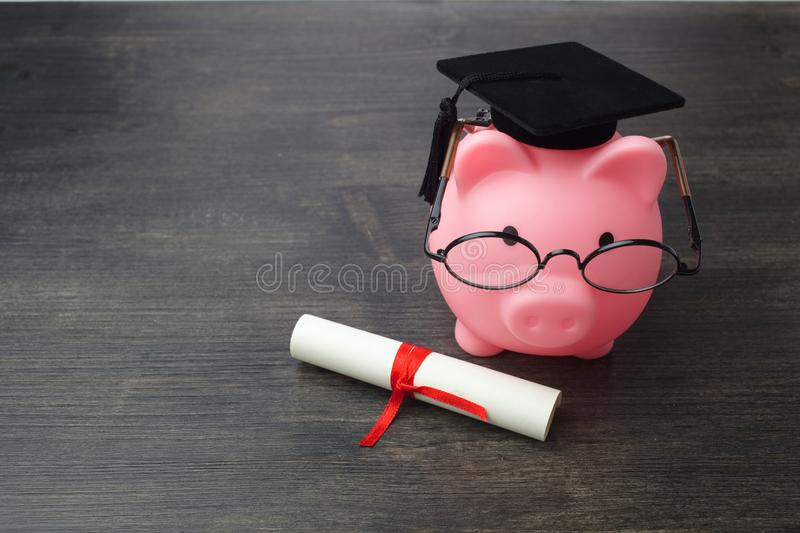 Piggy bank with a grad cap and diploma on wooden table, Education scholarship. Piggy bank with a grad cap and diploma on wooden table royalty free stock photos