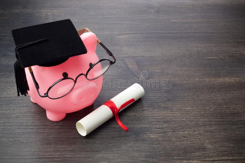 Piggy bank with a grad cap and diploma on wooden table, Education scholarship. Piggy bank with a grad cap and diploma on wooden table stock photos