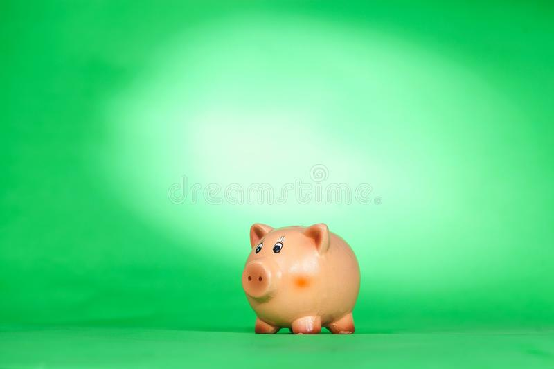 Piggy bank on green background royalty free stock photo