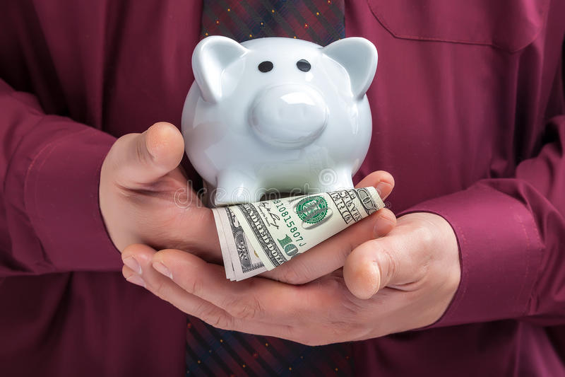 Piggy bank in the hands of a man in a shirt and tie stock image