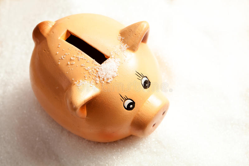 Piggy bank in a heap of sugar stock image