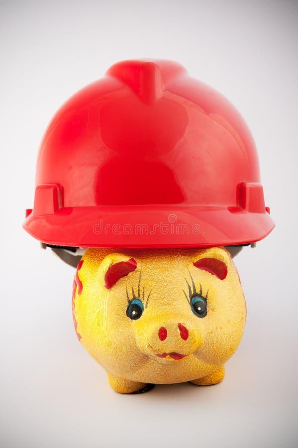 Piggy bank in helmet stock photography