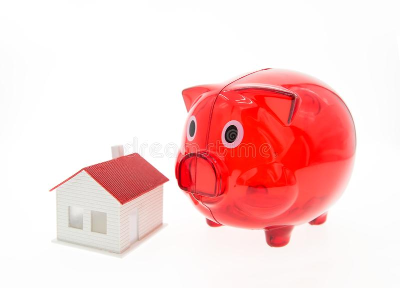 Piggy bank and a house on white stock photography