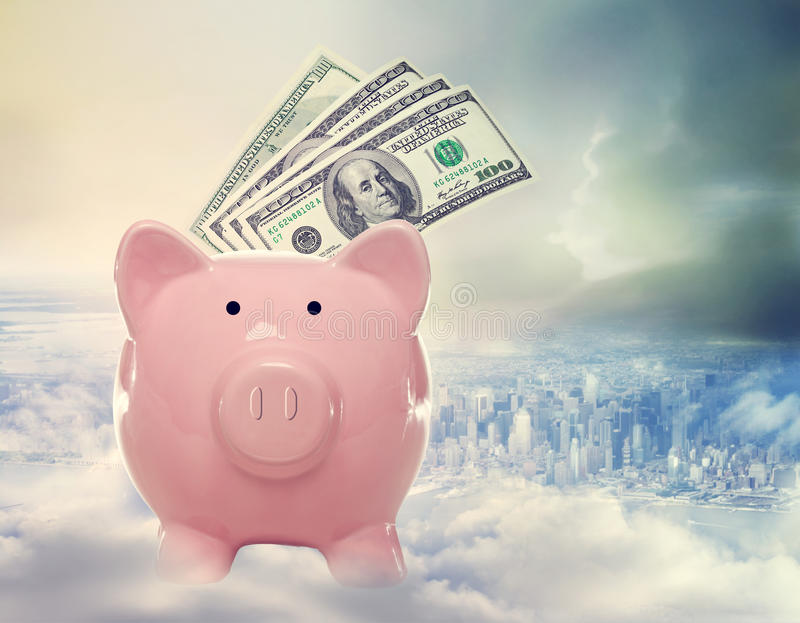 Piggy bank with hundred dollar bills above the city royalty free stock photos