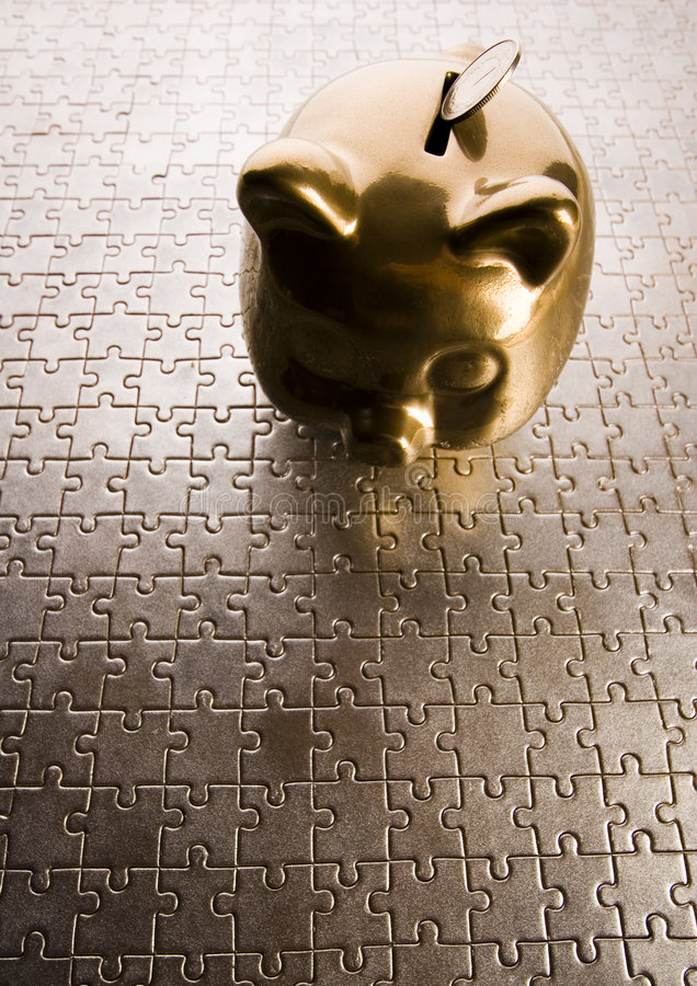 Piggy bank on jigsaws royalty free stock photography