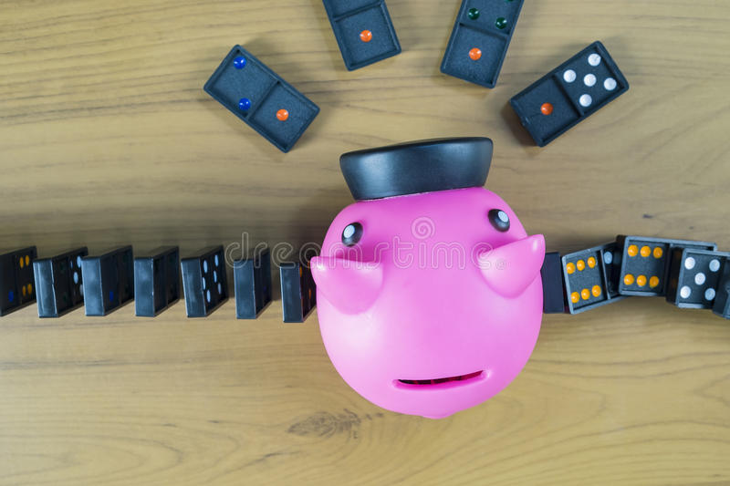 Piggy bank knocking out dominoes. Strategy and successful intervention stock photography