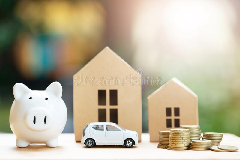 Piggy bank, Little toy car, money coins stacked on each other in different positions, house in paper model on the wooden table. Cr royalty free stock image
