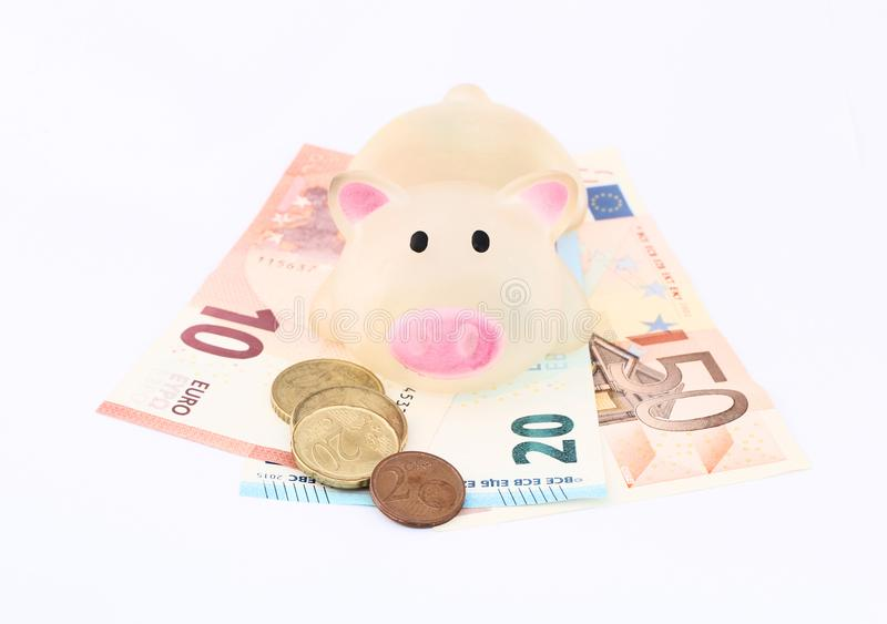 Piggy bank looking into lens with Euro coins and notes stock photo