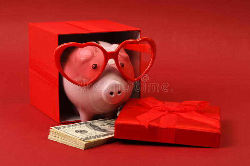 Piggy bank in love with red heart sunglasses standing in gift box with ribbon and with stack of money american hundred dollar bill royalty free stock photos