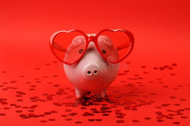 Piggy bank in love with red heart sunglasses standing on red background with shining red heart glitters stock image