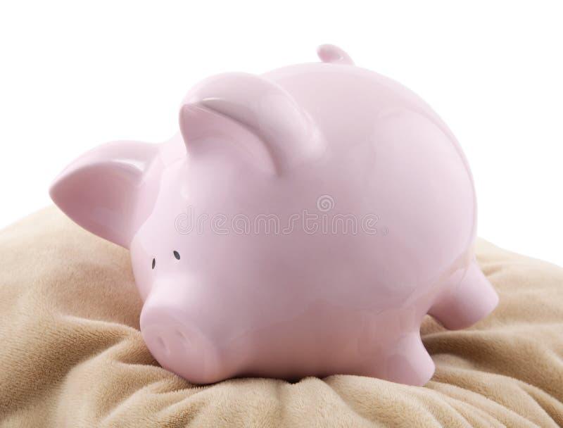 Piggy bank lying down on a pillow stock photos