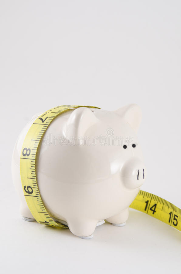Piggy bank with measure tape royalty free stock photo