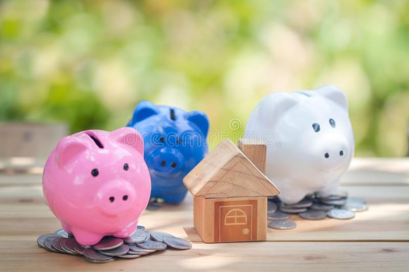 Piggy bank, Model of house with coins on wooden table on blurred background. Money Saving Ideas for Homes stock photography