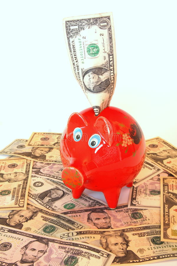 Piggy bank money. Lots of dollars in and around the piggy bank stock photo