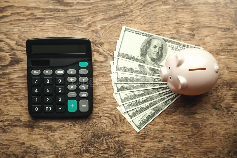 Piggy bank with money and calculator on wooden desk. Save your money royalty free stock image