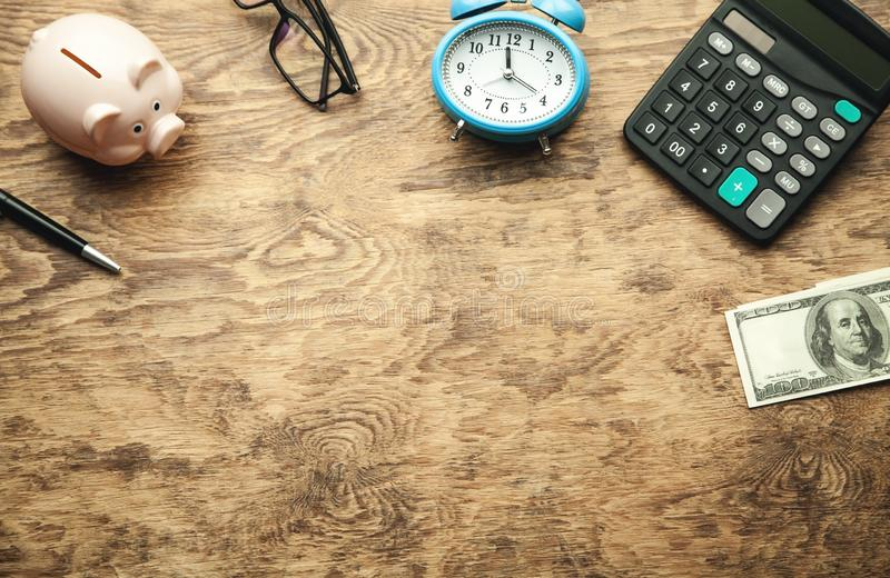 Piggy bank with money and calculator on wooden desk. Save your money stock image