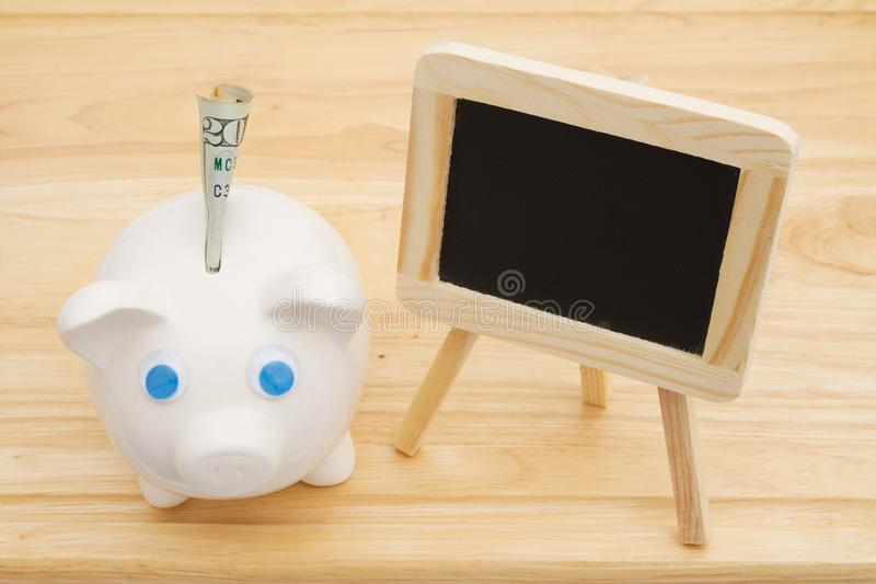 A piggy bank with money on a desk with chalkboard royalty free stock photography