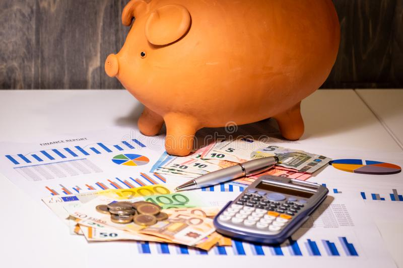 Piggy bank on money, euros bills, bussiness reports, pen and calculator royalty free stock photography