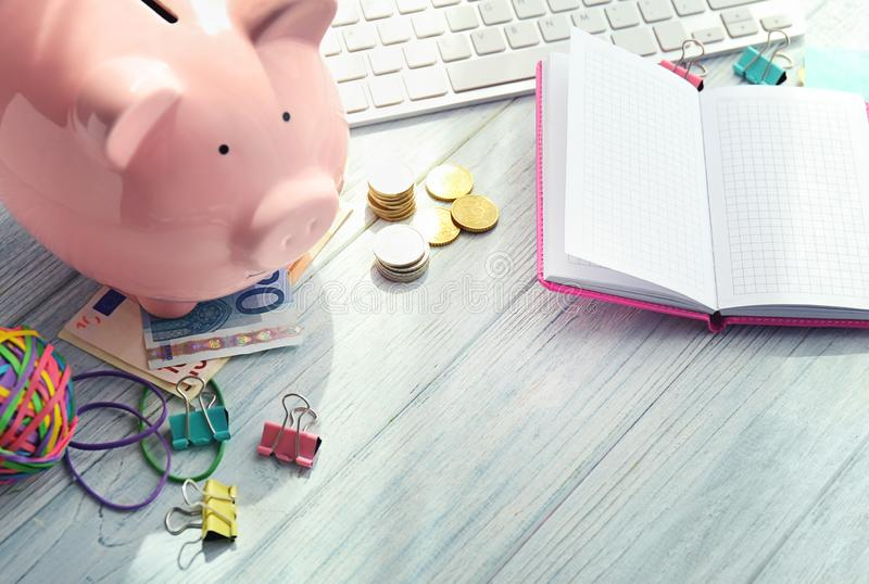 Piggy bank, money and notebook on wooden table. Concept of savings stock photos