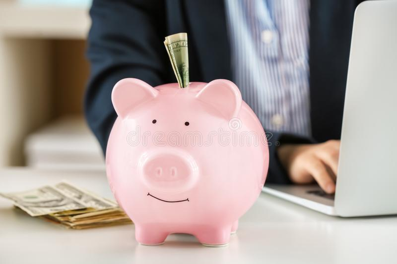 Piggy bank with money on table. Savings concept royalty free stock photography