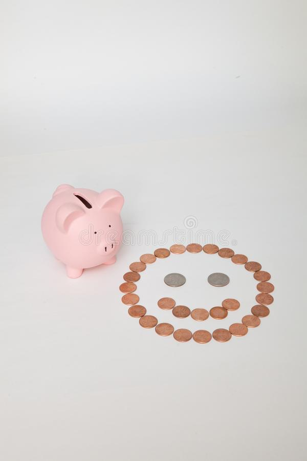 Piggy Bank next to a Smiley Face royalty free stock image