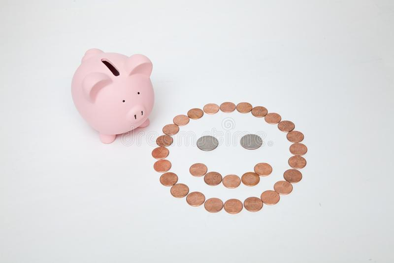 Piggy Bank next to a Smiley Face royalty free stock images