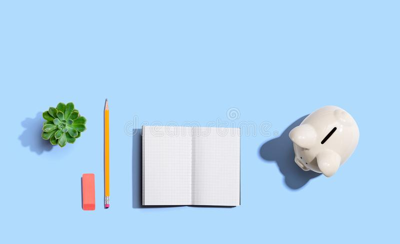 Piggy bank with office supplies. From above royalty free stock image