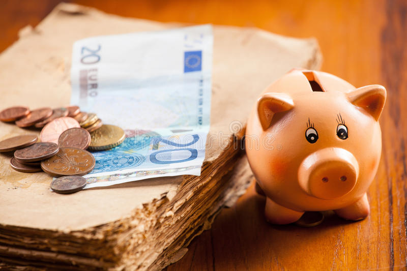 Piggy bank by the old book and euros banknote and pile of coins royalty free stock photo