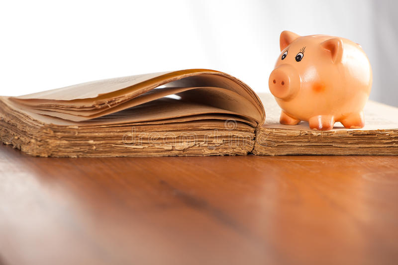 Piggy bank on the old book stock image