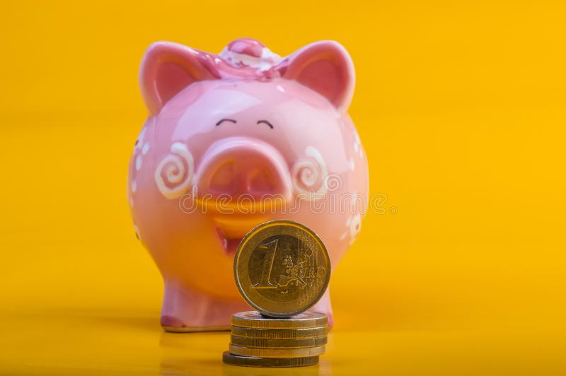Piggy bank and one euro on a pile of coins. Yellow background. C royalty free stock photo