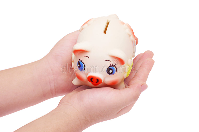 Piggy bank in the palms of child s hand