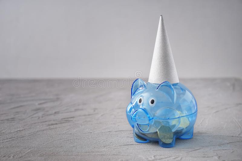 Piggy bank with party hat on table. Concept of saving money for holiday royalty free stock images