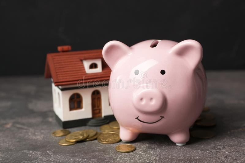 Piggy bank with pile of coins and house model. On table stock images