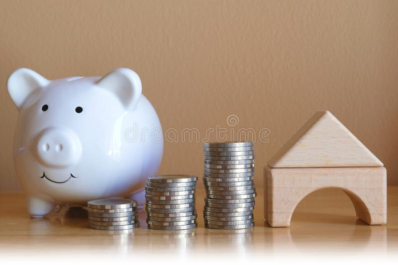Piggy bank and pile of coins with wooden house shape. Home finance and mortgage concept. Property investment. Copy space stock photography