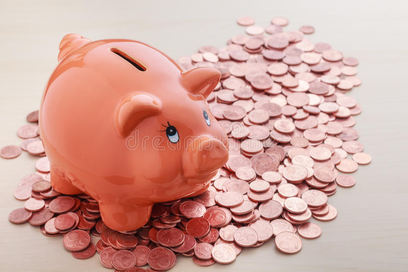 Piggy bank on pile of euro cents coins stock photography
