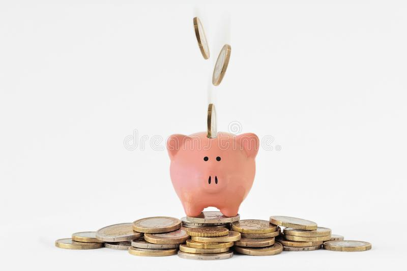Piggy bank on pile of money and falling euro coins royalty free stock image