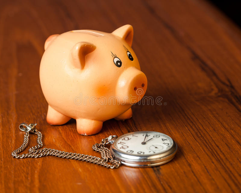 Piggy bank and pocket watch royalty free stock image