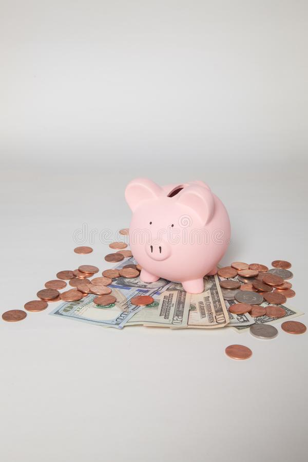 Piggy Bank on pile of bills and coins royalty free stock images