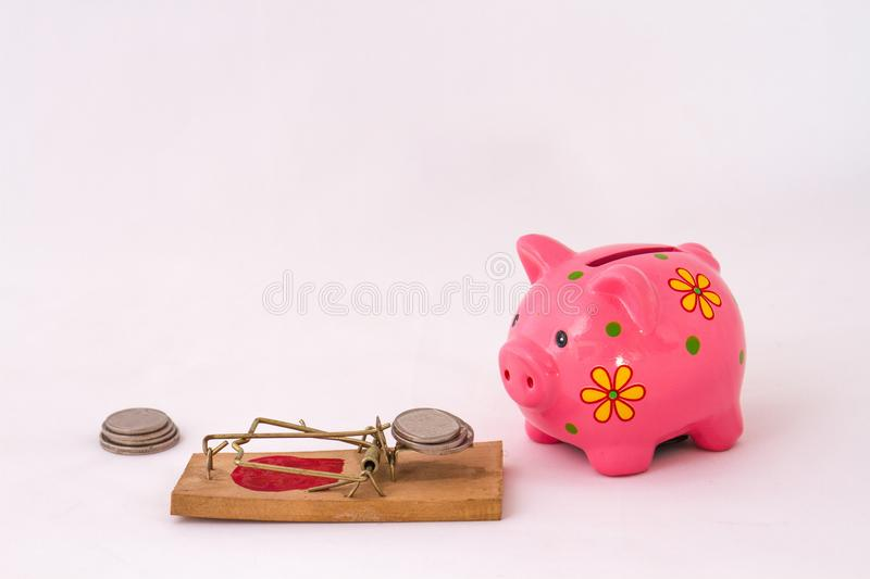 Retirement savings concept with piggy bank and coins. A piggy bank and some coins retirement savings concept image with copy space in landscape format on a white stock photo