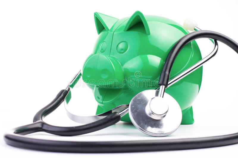 Piggy Bank With Stethoscope. On white isolated background stock photos